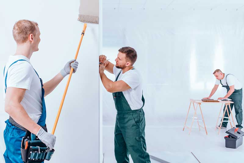 Painter with Roller Painting a Wall while Redecorating Interior Office Building